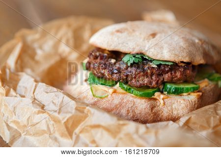 Classic american fast food closeup background. Burger whole grain bun with grilled on barbecue meat and onions on wood in craft paper. Hamburger with fresh vegetables composition.
