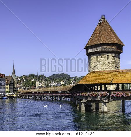 Landmarks of the city of Lucerne Switzerland: the Chapel Bridge and the Water Tower St. Peter Chapel and St. Leodegar Cathedral in the background.