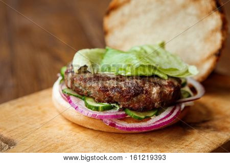 Classic american fast food background. Burger with roasted open bun and grilled on barbecue meat with onions, closeup on wooden cutting board. Hamburger with fresh vegetables. Shallow depth of filed