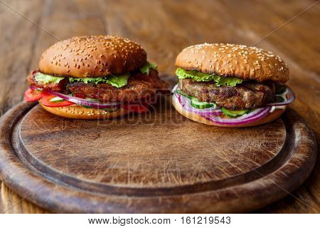 Classic american fast food background. Burgers with grilled on barbecue meat and onions on wood. Hamburgers with fresh vegetables composition.