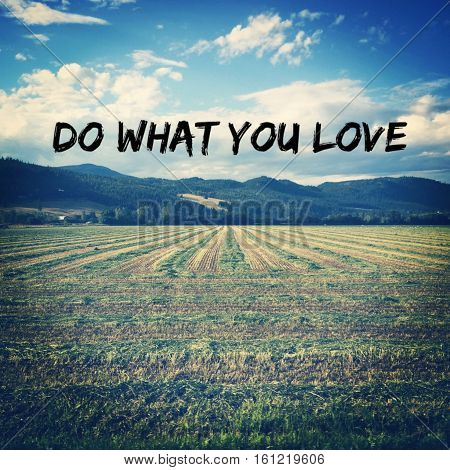 Do what you love. Conceptual image.  Inspirational quote on plowed farm field in summer with blue sky, white coulds and hills background. Instagram effects