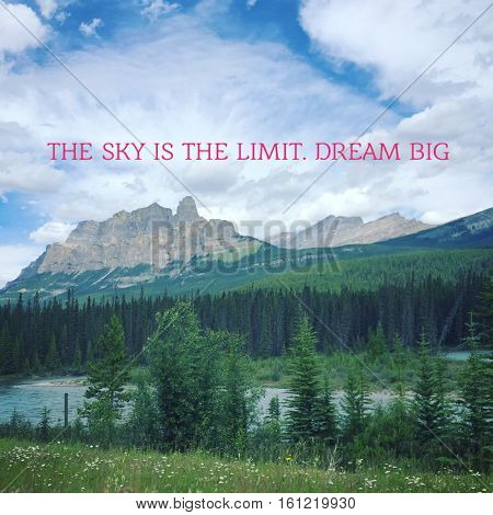 The sky is the limit. Dream big. Inspirational quote on beautiful scenic summer mountain landscape with sunshine on mountain peaks and lush trees, river and blue sky clouds background.