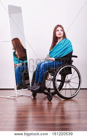 Disability disease wheelchair sad tragedy concept. Disabled girl looking at relfection holding hair comb. Young fashionable crippled girl in blue scarf in front of mirror.