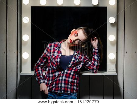 Young caucasian girl with stage make-up. A woman in a plaid shirt standing near the mirror.
