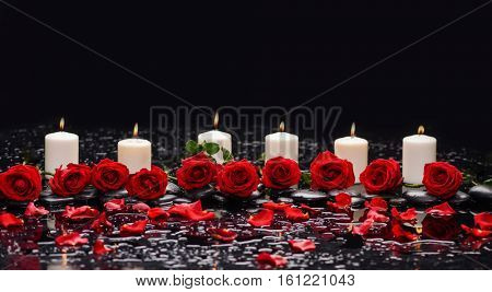 Still life with row of red rose with candle and therapy stones