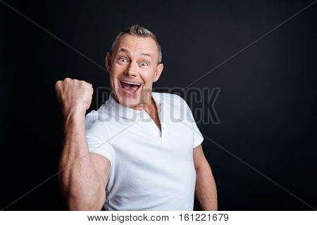 Yes man. Cheerful delighted handsome senior man expressing jubilation and using his gestures while smiling
