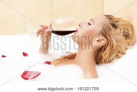 Sexual Caucasian Blond Woman in Foamy Bathtub with Flowers Petals Drinking Red Wine.Horizontal Image Orientation