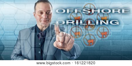 Happy mature corporate manager touching OFFSHORE DRILLING on an interactive remote control monitor. Oil and gas production metaphor and petroleum industry concept for subsea drilling operations.