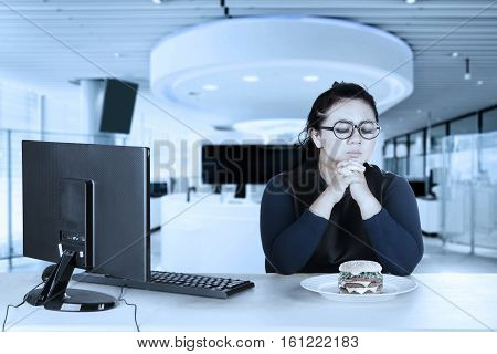Image of a hesitated female entrepreneur tries to diet and tempted with cheeseburger while working with a computer in the workplace