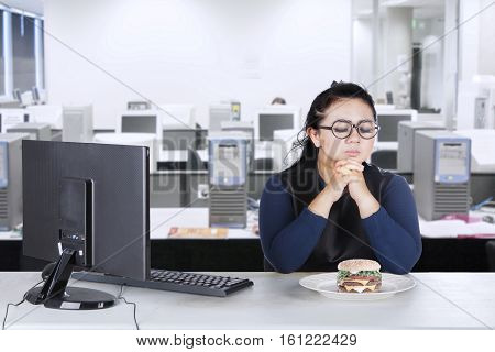Picture of obesity businesswoman with computer and hesitate to eat cheeseburger in the workplace