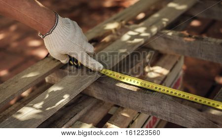 Man's hand doing measure of wooden plank with ruler. Carpentry construction.