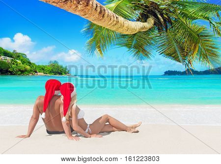 Romantic couple in red Christmas Santa hats hugging and tanning at island tropical palm sandy beach Seychelles Indian Ocean. Happy New Year holidays travel destinations concept.