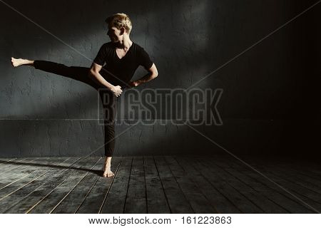 Involved in dancing. Talented expressive graceful man dancing in the dark lighted room and stretching while showing his flexibility