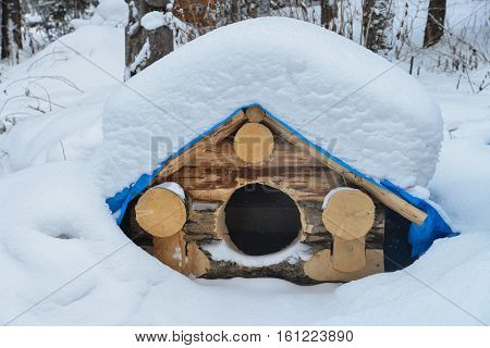 Dog house in the winter with snow on roof.