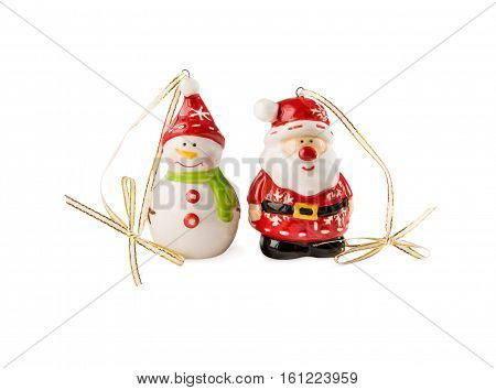 Christmas and New Year's decorations. Funny Snowman and Santa Claus toys made of porcelain isolated over white.