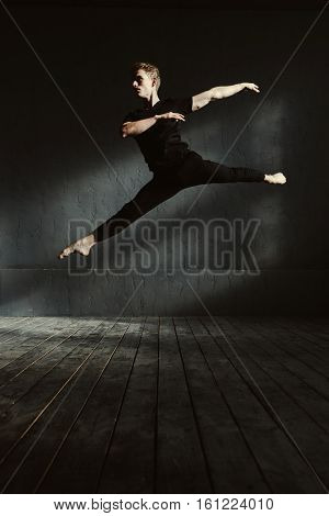 Routine of a ballet dancer. Flexible skillful concentrated man performing in the dark lighted room and dancing while showing his abilities in the air