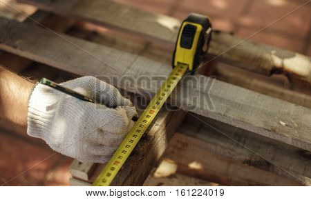 Man doing measure with pencil and ruler carpentry construction woodwork.