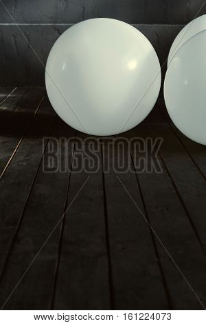 Balloons for performance. White big inflated balloons lying in the dark lighted studio and shining