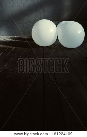 Balloons in the studio. White big inflated balloons located in the dark lighted studio and shining