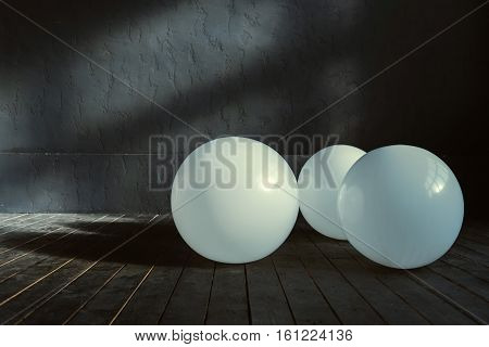 Shining balloons . Big white inflated balloons located in the dark lighted studio and shining