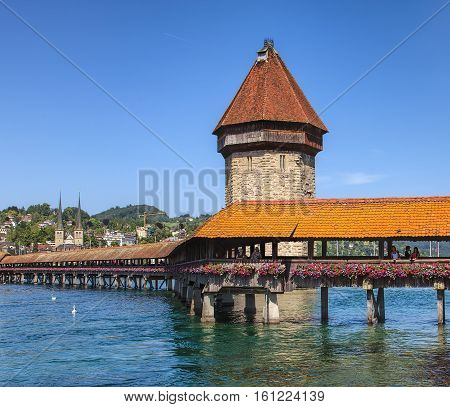 Lucerne, Switzerland - 10 June, 2014: landmarks of the city - the Chapel Bridge and the Water Tower, St. Leodegar Cathedral in the background. Lucerne is a city in central Switzerland it is the capital of the Swiss Canton of Lucerne.