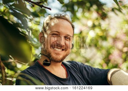 Portrait of happy caucasian man with headphones in the garden nature background lifestyle. People concept.