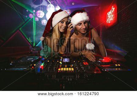 DJ Santa mixing up some Christmas cheers with santa helper.