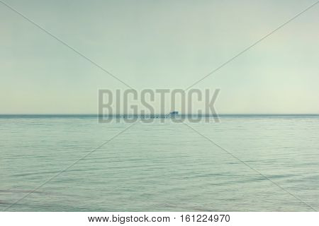 At sea, the rain. ozhdlivaya gray weather. Seascape. On the horizon is a cargo ship, a cargo ship. Foggy weather. Over the edge of the sea flying flock of birds. Flock of ducks.