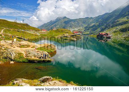 BALEA LAKE ROMANIA - 21 JULY 2014: Unidentified tourists enjoy the sights of Balea Lake at 2034 m altitude in Fagaras Mountains Romania.