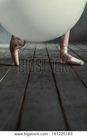 Elegant ballet dancer legs and the balloon. Big white inflated balloon located in the dark lighted studio and shining while lying near the ballet dancer legs wearing in the pointe