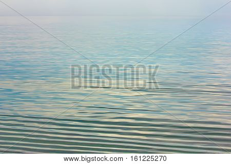Mirror Sea Surface or river. The water reflects the sky and clouds. On the sea calm, the water ripples. Landscape seascape. The sky and water blue and gray.