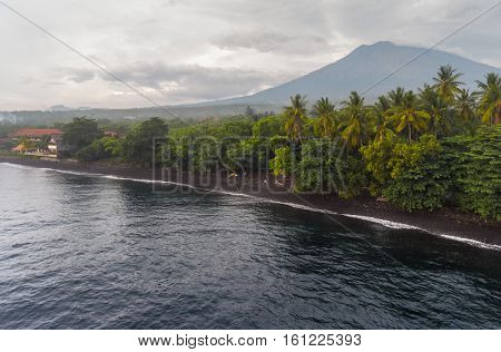 Aerial shot of the coast with beach and volcano of Agung on the horizon, Bali, Indonesia