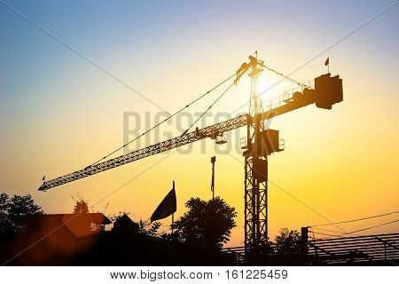 Silhouette Tower Crane industry engineer on background for concept.city work life win team sky blurred technology sunsrt real worker urban success site high five deal over person metal night crane.