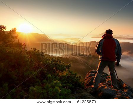 Happy photo enthusiast enjoy photography of fall daybreak in nature on cliff on rock. Dreamy fogy landscape misty sunrise in a beautiful valley below