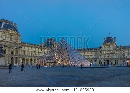PARIS, FRANCE - DECEMBER 8, 2016: View of famous Louvre Museum with Louvre Pyramid at evening. Louvre Museum is one of the largest and most visited museums worldwide.