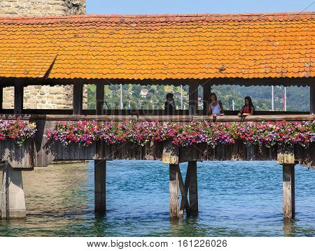 Lucerne, Switzerland - 10 June, 2014: people on the famous Chapel Bridge. The Chapel Bridge is a covered wooden footbridge across the Reuss river in the Swiss city of Lucerne, named after the nearby Saint Peter's Chapel.