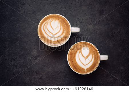 Two cups of coffee on black rustic background with beautiful latte art