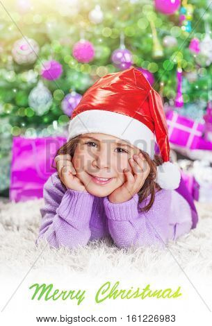 Little girl lying down near Christmas tree at home, little Santa helper wearing red festive hat, Christmastime photo with text space, best wishes on winter holidays