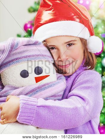 Closeup portrait of a cute little baby girl wearing red Santa hat near festive decorated Christmas tree, with love hugging her soft snowman toy, enjoying Xmas present, happy winter holidays