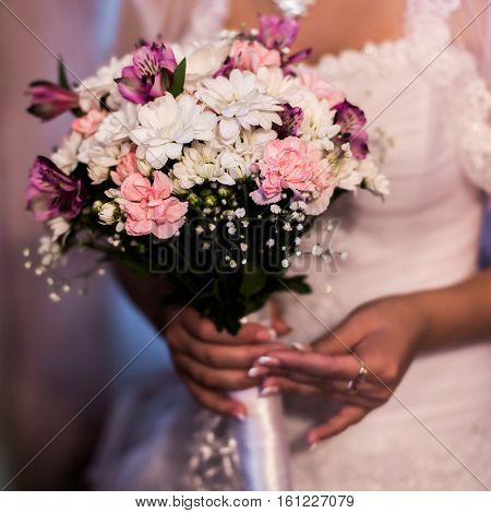 the bride holding a bouquet of white pink and mauve flowers women's hands and a bouquet of flowers the morning of the bride