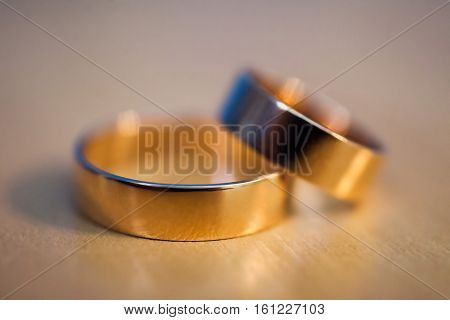 gold wedding rings wedding bands on a yellow background rings on the couch