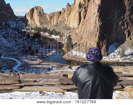 A woman in a fuzzy purple hat enjoys the grand view at Smith Rocks State Park in Central Oregon with the snowy jagged and rugged cliffs and the Crooked River peacefully flowing below.