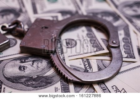 money and the law handcuffs on money hundred dollar bills front side and handcuffs. background of dollars savings taxes and law close up