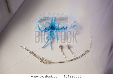 Garter of the bride women's earrings and chain lie on a white background wedding decorations are on the windowsill fees bride preparing for the wedding wedding jewelry