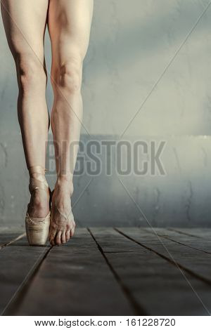 Toe dance hurts. Proficient gifted skilled ballet dancer demonstrating her leg in pointe and another naked leg while standing isolated on the tiptoes on the black floor and performing