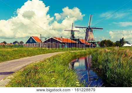 Picturesque rural landscape with windmills in Zaanse Schans close to canal, Holland, Netherlands. Used toning