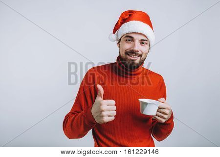 Winter concept - Christmas holiday. Handsome man in the red sweater wearing Santa's hat holding a large cup of tea and showing everything is ok. Isolated on white background