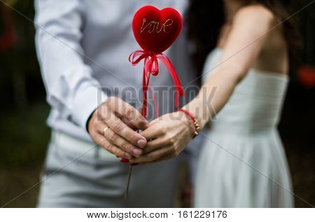 a man and woman holding a heart in his hands the love between a man and a woman