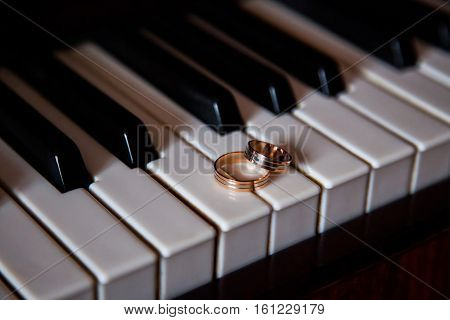 gold wedding rings wedding bands on a black and white background rings lie on the piano keys rings in an unusual background