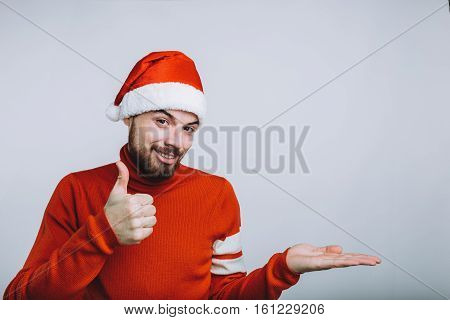 Winter concept - Christmas holiday. Happy man is wearing Santa's hat and red sweater. He is showing with his thumb that everything is ok or cool. Isolated on white background